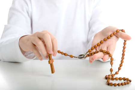 long sleeved: A Hispanic boy holds Rosary beads with both hands. He wears long sleeved shirt