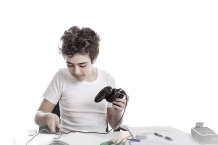 short sleeve: Caucasian boy in short sleeve t-shirt plays with a game controller sitting in front of his  homework on desk Stock Photo