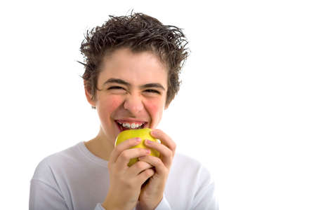 sleeved: A handsome Caucasian boy wearing a long sleeved white shirt is goingt to bite and eat a yellow apple with both hands while laughing Stock Photo