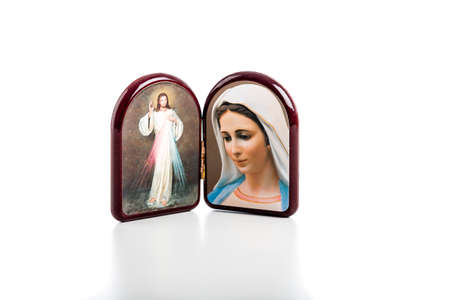 Icons in a wooden rounded case of Merciful Jesus and Our Lady of Medjugorje, the Blessed Virgin Mary isolated on white background with matte reflection on white table. Imagens