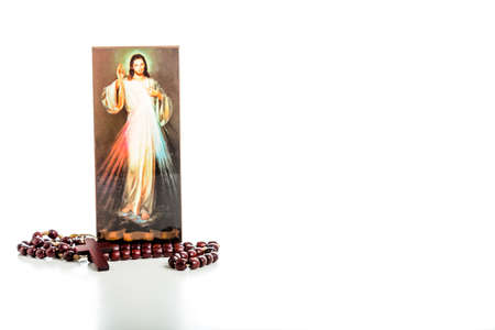 Brown Rosary beads and a picture of the Merciful Jesus: the translation of the Italian writing on bottom is Jesus, I trust in you Foto de archivo