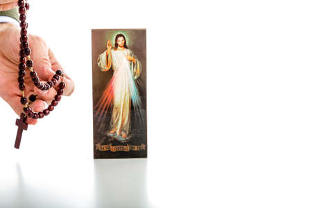 Hand offering brown Rosary beads and a picture of the Merciful Jesus: the translation of the Italian writing on bottom is Jesus, I trust in you