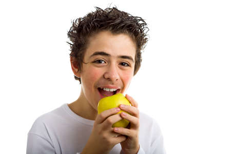 long sleeved: A handsome Caucasian boy wearing a long sleeved white shirt is goingt to bite and eat a yellow apple with both hands