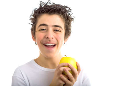 long sleeved: A handsome Caucasian boy wearing a long sleeved white shirt holds a yellow apple with both hands Stock Photo