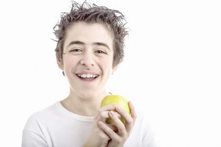 sleeved: A handsome Caucasian boy wearing a long sleeved white shirt holds a yellow apple with both hands Stock Photo