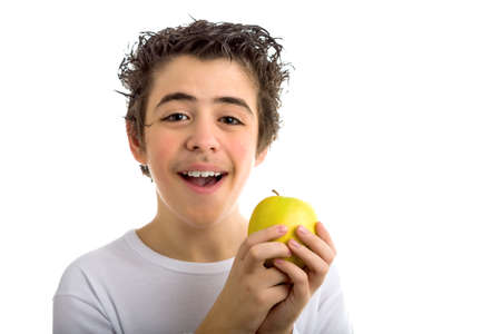 long sleeved: A cute Caucasian child wearing a long sleeved white shirt holds a yellow apple with both hands