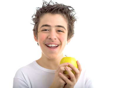 long sleeved: A handsome Caucasian kid wearing a long sleeved white shirt holds a yellow apple with both hands Stock Photo