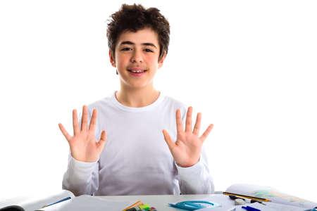 number ten: Am�rica cauc�sica adolescente muchacho sentado mientras se hace la tarea es feliz y muestra el n�mero diez con los dedos Foto de archivo