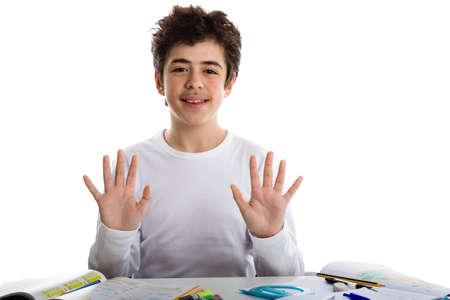 numero diez: América caucásica adolescente muchacho sentado mientras se hace la tarea es feliz y muestra el número diez signo con los dedos