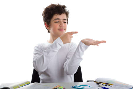 trustable: Cauc�sica joven latino se sienta frente a la tarea, sonr�e de una manera confiable y con el dedo �ndice indica algo que est� trayendo en su mano izquierda