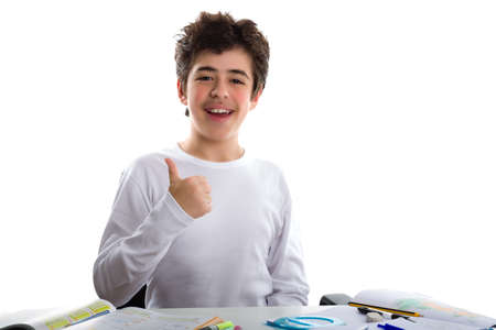 Caucasian latin young boy sits in front of homework, smiles  and feels happy  showing success with his thumb finger to viewers