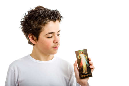 the merciful: A hispanic boy holds a picture of Merciful Jesus