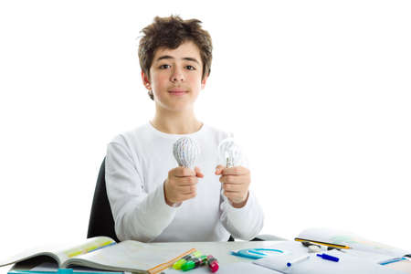dishevelled: Smiling Caucasian boy wearing a white long sleeve t-shirt is holding a real glass lightbulb and a 3D print prototype while sitting in front of his homework