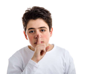 long nose: Caucasian teenager with acne skin in a white long sleeve t-shirt asks for silence touching his nose with  his right finger Stock Photo