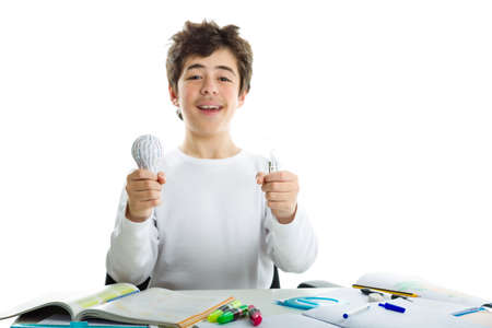 rapid prototyping: Smiling Caucasian boy wearing a white long sleeve t-shirt is holding a real glass lightbulb and a 3D print prototype while sitting in front of his homework