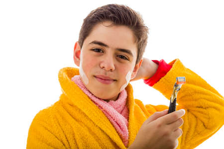 red bathrobe: A Hispanic boy wears a yellow bathrobe with a pink towel around his neck: he has some patches on his face but smiles holding the razor he used for shaving Stock Photo
