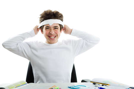 dishevelled: Before doing homework, handsome Caucasian boy is smiling and tying around the forehead a white handkerchief as the band usually used by Japanese suicide bombers during World War. Stock Photo