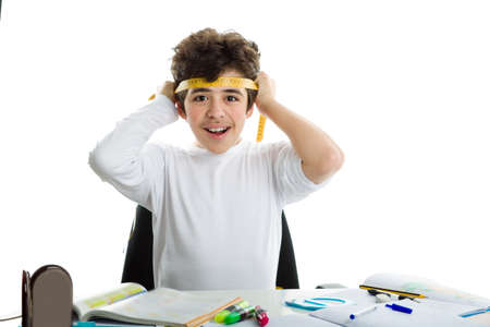 forehead: Before doing homework, handsome Caucasian boy is smiling and tying around the forehead a yellow measure tape in a similar way as Japanese suicide bombers did during World War. blank icon in the foreground Stock Photo