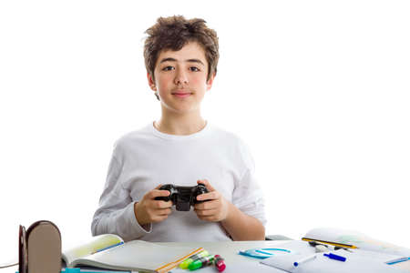 short sleeve: Happy caucasian boy in short sleeve t-shirt plays with a game controller sitting in front of his  homework on desk