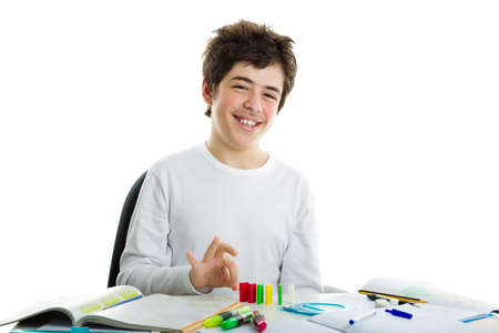 dishevelled: Smiling Caucasian boy wearing a white long sleeve t-shirt is playing with dominoes on homework Stock Photo