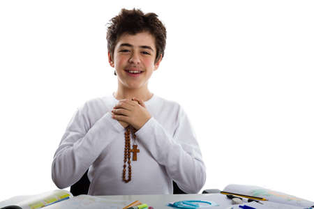 clasped: Caucasian boy is doing homework: sitting in front of a desk covered by book, copybooks, erasers and pencils, he prays with clasped hands holding  Catholic Rosary beads Stock Photo