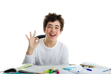 all right: Caucasian latin young boy sits in front of homework, smiles  and feels happy  showing OK, all right, sign Stock Photo