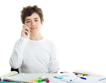 white long sleeve: Handsome Hispanic boy is talking on cell phone while doing homework and wearing a white long sleeve t-shirt