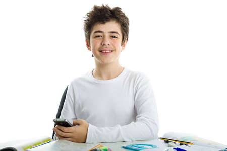 white long sleeve: Handsome Caucasian boy sits in front of homework wearing a white long sleeve t-shirt and smiles using his cell phone, a smartphone