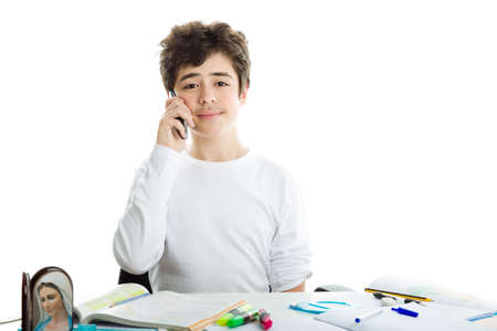 dishevelled: Smiling handsome Hispanic boy is talking on cell phone while doing homework and wearing a white long sleeve t-shirt Stock Photo