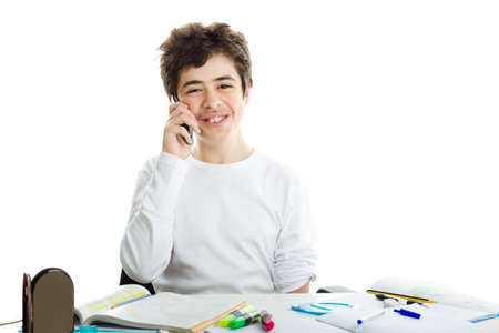 white long sleeve: Smiling handsome Hispanic boy is talking on cell phone while doing homework and wearing a white long sleeve t-shirt Stock Photo