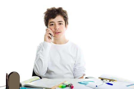 long sleeve: Handsome Hispanic boy is talking on cell phone while doing homework and wearing a white long sleeve t-shirt