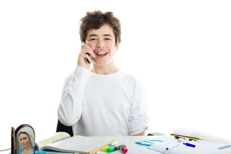 dishevelled: Smiling handsome Hispanic boy is talking on mobile phone while doing homework and wearing a white long sleeve t-shirt