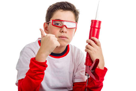 caulk: A boy wearing red googles holds a red caulk gun with right hand while he makes success sign with right hand: he looks a calm and confident professional