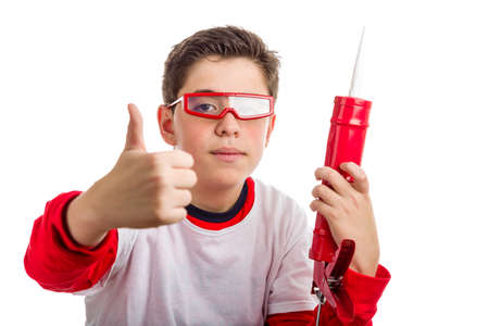 caulk: A boy wearing red googles holds a red caulk gun with right hand smiling while he makes success sign with right hand