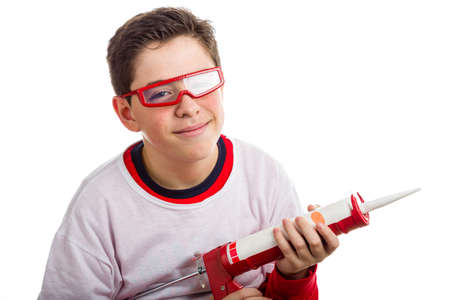caulking: A Hispanic boy wears red googles with clear lenses and with right hand smiling  he holds a red caulking gun Stock Photo