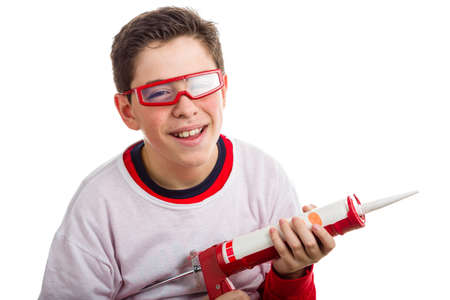 caulk: A Hispanic boy wears red googles with clear lenses and with right hand smiling  he holds a red caulking gun Stock Photo