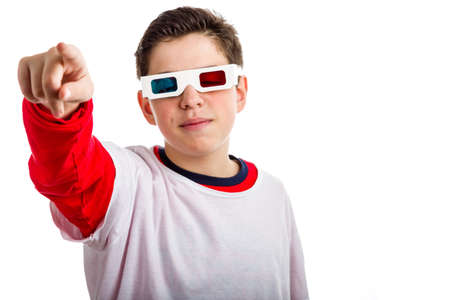 looking at viewer: A Caucasian boy wears a pair of 3D Cinema paper googles with red and sky-blue lenses and looking calm and confident points to viewer with right hand