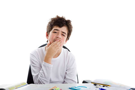 dishevelled: Tired Caucasian boy sits in front of homework wearing a white long sleeve t-shirt and yawns covering his mouth with right hand