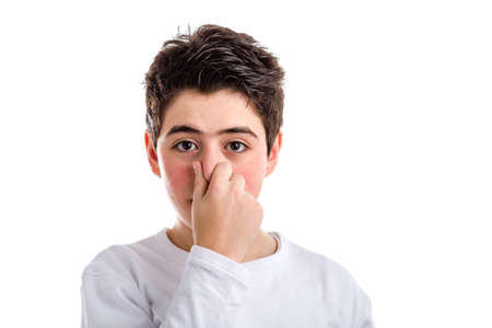 plugging: Caucasian boy with acne skin in a white long sleeve t-shirt is plugging his nose  with right hand Stock Photo