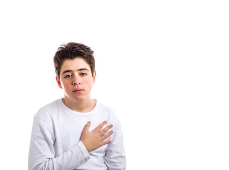 hairy chest: Handsome Caucasian boy with acne-prone skin in a white long sleeved t-shirt keeping his right hand on the heart