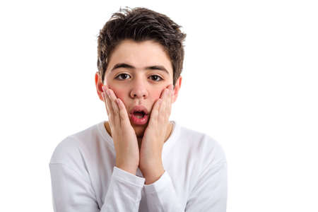 bewildered: Bewildered Caucasian boy with acne-prone skin in a white long sleeved t-shirt gapes placing hands on the sides of the face