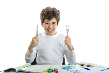 dishevelled: Smiling handsome Caucasian smooth-skinned boy wearing a white long sleeve t-shirt is going to do homework with fork and knife treating it as if it were food
