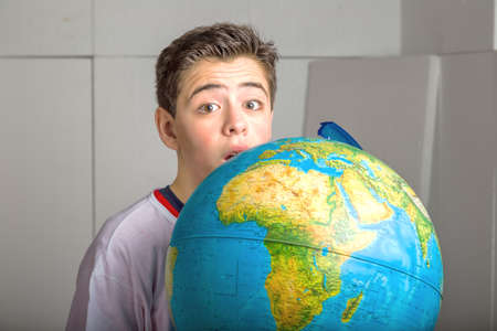 eyes hidden: Caucasian smooth-skinned boy hidden behind a globe reveals only the eyes and part of the face on industrial background Stock Photo