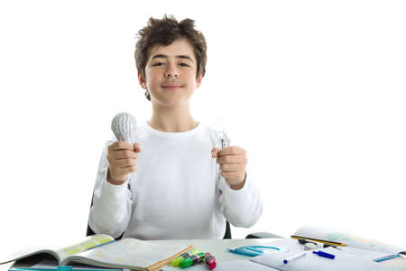 Smiling Caucasian smooth-skinned boy wearing a white long sleeve t-shirt is holding a real glass lightbulb and a 3D print prototype while sitting in front of his homework
