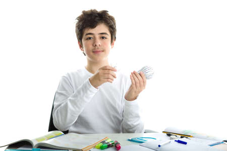 dishevelled: Smiling Caucasian smooth-skinned boy wearing a white long sleeve t-shirt is holding a real glass lightbulb and a 3D print prototype while sitting in front of his homework