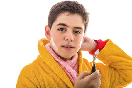 A Caucasian smooth-skinned boy wears a yellow bathrobe with a pink towel around his neck: he has some patches on his face but smiles holding the razor he used for shaving photo