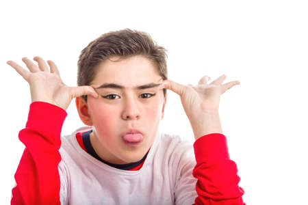 long sleeved: Caucasian smooth-skinned boy wearing red long sleeved shirt makes faces with both hands showing his tongue Stock Photo