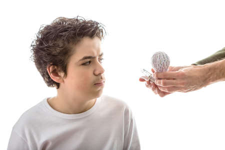 rapid prototyping: A Caucasian smooth-skinned boy takes a puzzled look to 3D prototype and real lightbulb that adult hand is giving to him from his left side Stock Photo