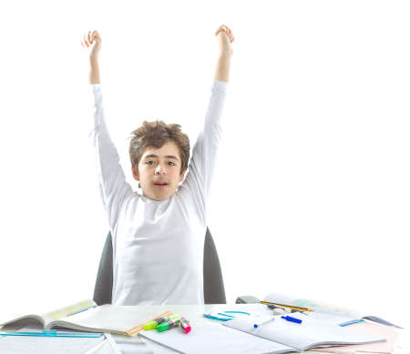 dishevelled: Handsome Caucasian smooth-skinned boy wearing a white long sleeve t-shirt boy is raising arms in front of homework Stock Photo