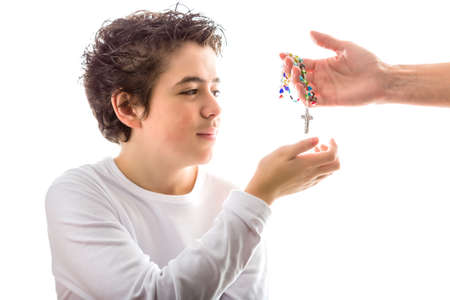 long sleeved: A happy Caucasian smooth-skinned boy wearing a white long sleeved t-shirt smiles receiving with his right hand a Rosary made with glass beads given by bare adult hand